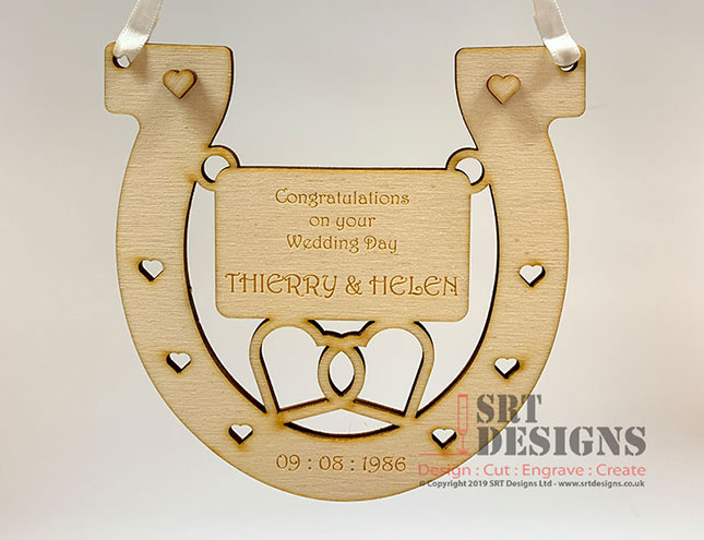 Wedding details on horseshoe with white satin ribbon for hanging.